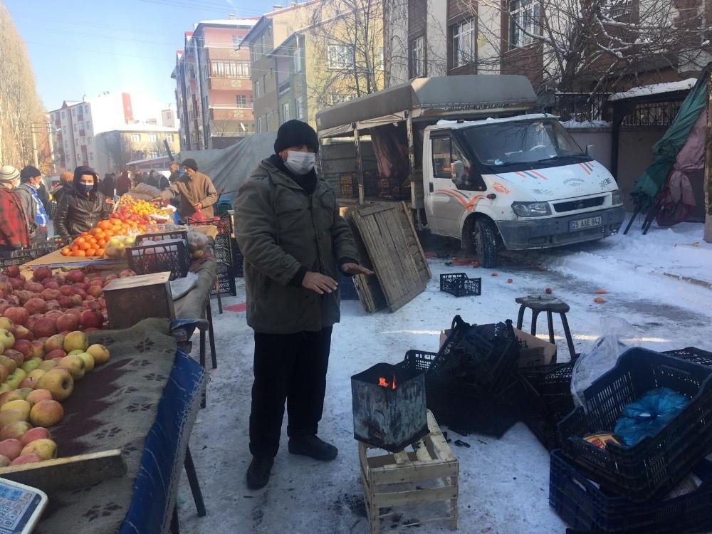 Pazarcılar soğuk havada açık alana kurdukları soba ile ısınıyor